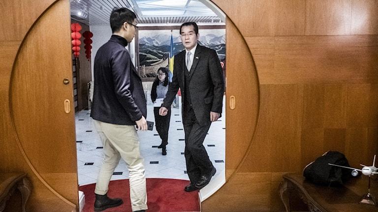 Two men walking through a circular doorway.