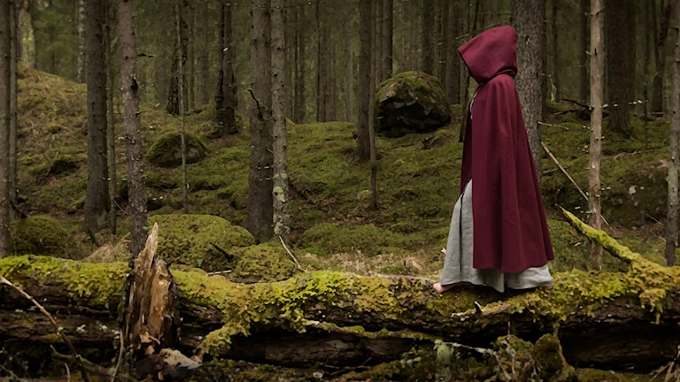 A woman in a red robe walks barefoot through the forest