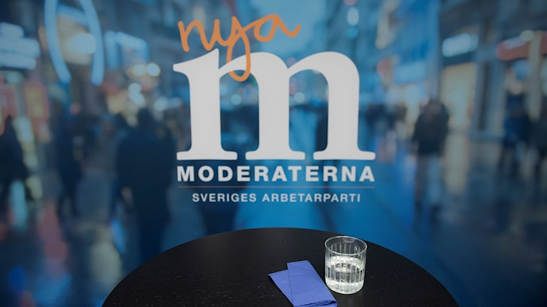A table with a napking and glass of water in front of a Moderate Party poster.