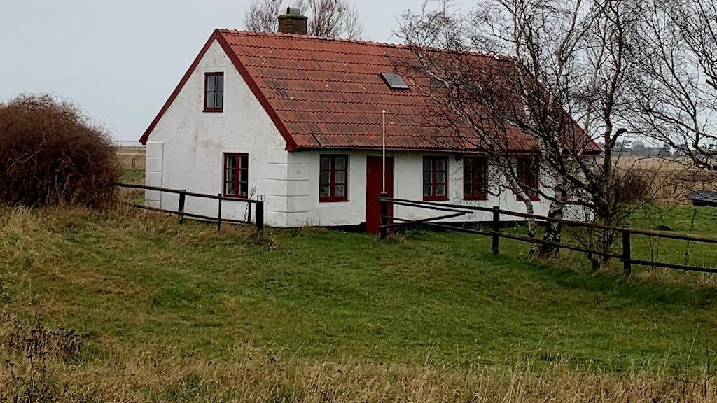 A picture of an older house standing in a field.