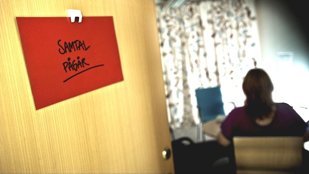 """En röd lapp med texten """"samtal pågår"""" sitter på en öppen dörr. Inne i rummet sitter en person på en stol med ryggen mot kameran."""