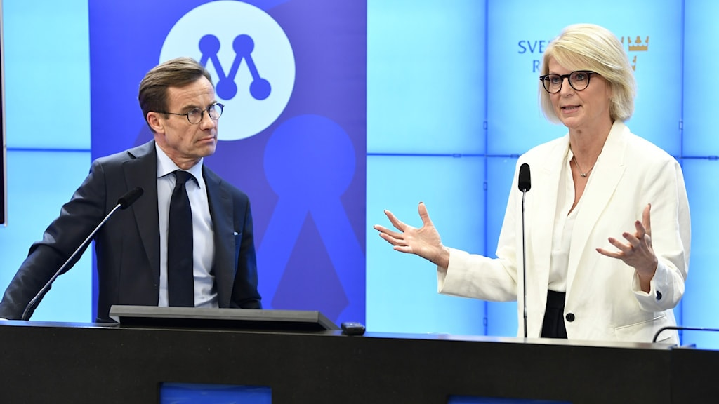 two people in business suits stand behind microphones. one of the people gestures with her hands.