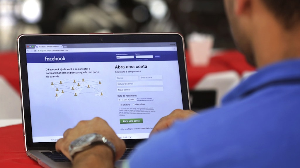 A person logging into Facebook on a laptop
