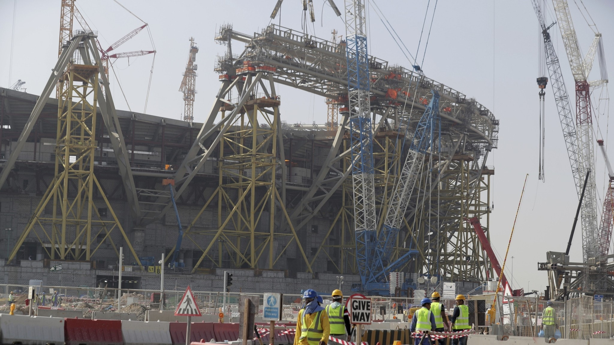 cranes and scaffolding around a stadium that is under construction. workers wearing bright vests in the foreground.