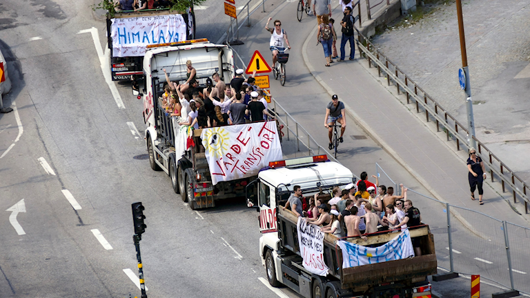 "View of three trucks filled with students in the back (""student floats"")."