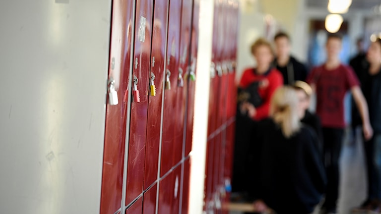 A school hallway with lockers and students in the background