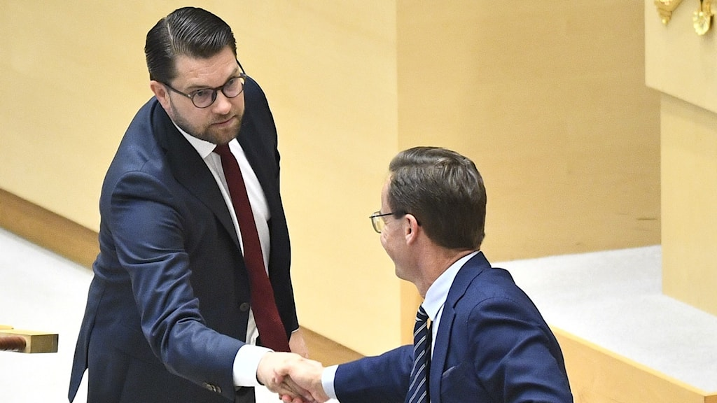 Jimmie Åkesson shakes Ulf Kristersson's hand in the Riksdagen.