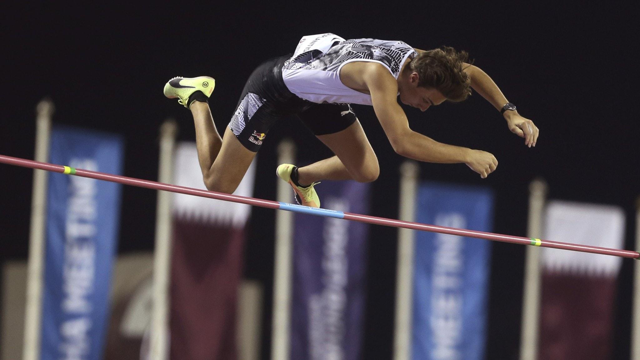 A man flying through the air over a horizontal bar.