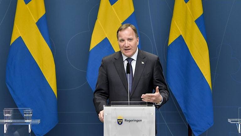 A man standing in front of three Swedish flags.