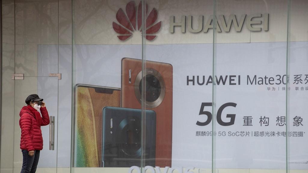 Person stå framför en skylt där Huawei för reklam för 5G-nätet.