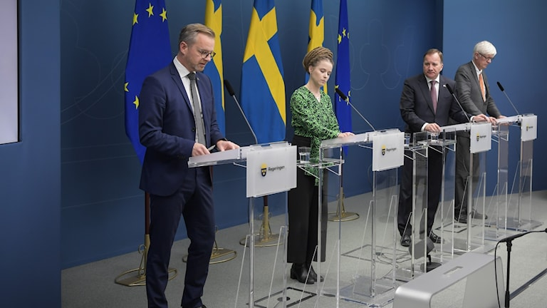 Ministers standing in front of Swedish flags.
