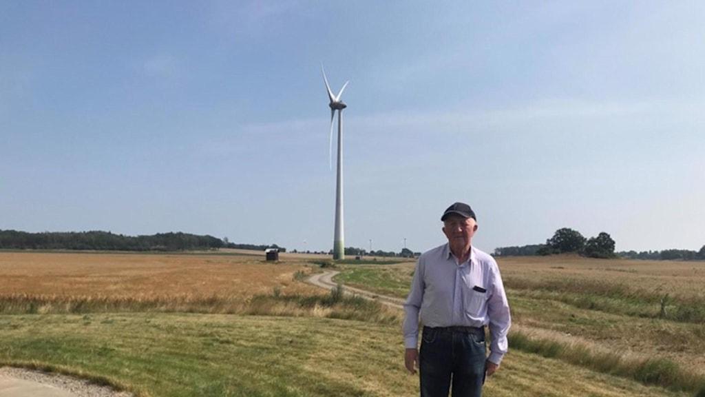 Nils-Erik Bondesson standing by a wind turbine
