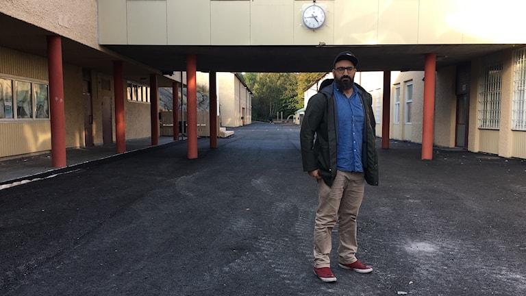 En man står på en skolgård med en klocka bakom sig.