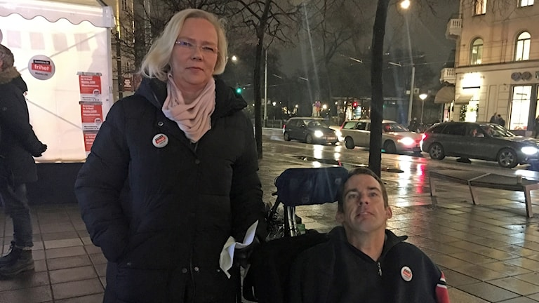 Woman, standing, and man, in a wheel chair, outdoors, looking into the camera.