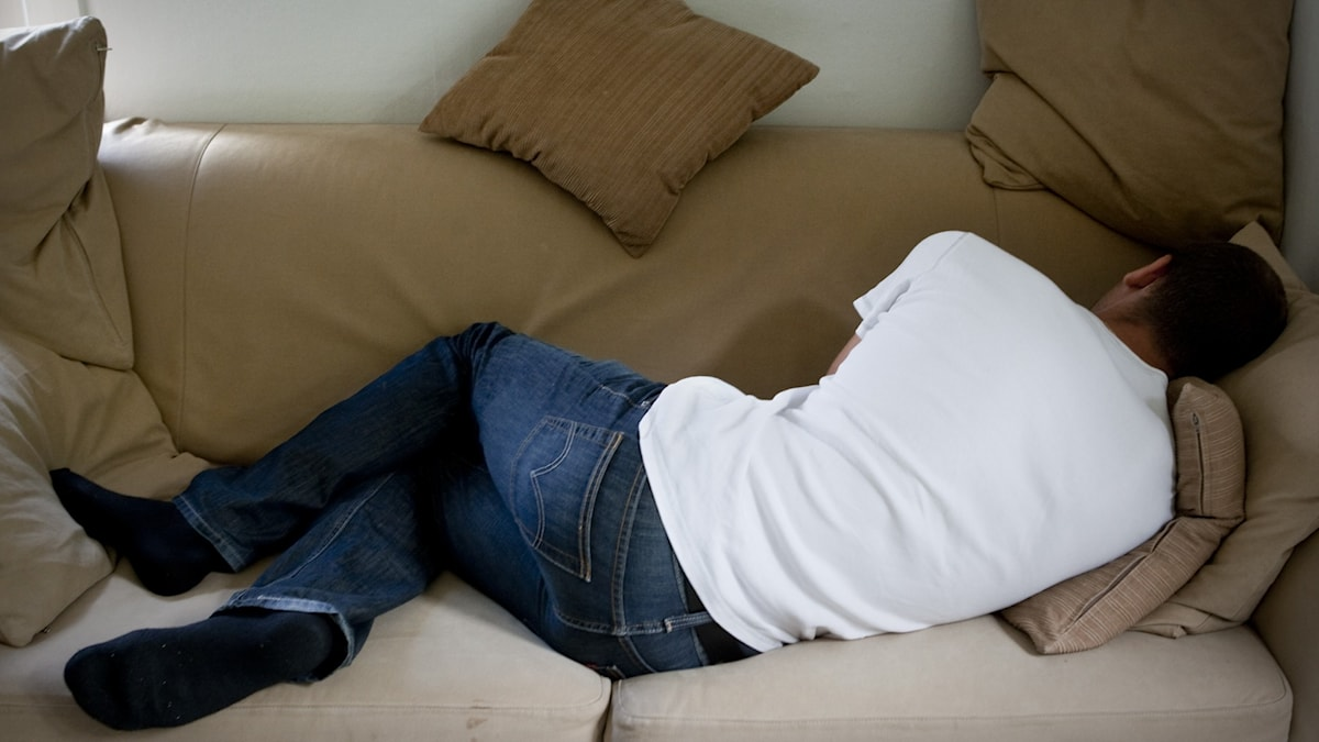 The back of a man lying on the couch.