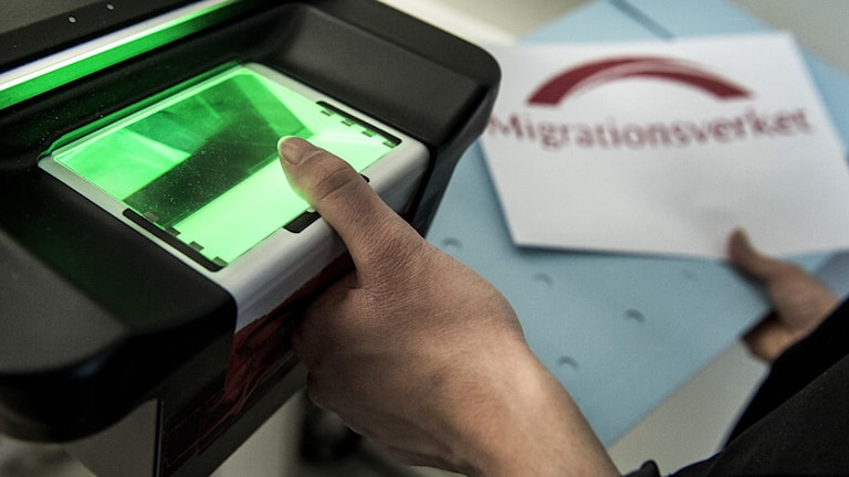 A person scanning their thumb at a Migration Agency office