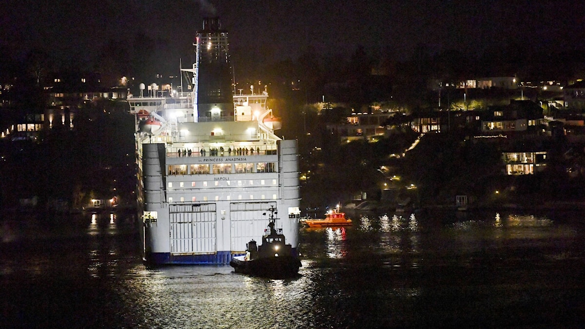 A nighttime photo of a lite ferry being towed.
