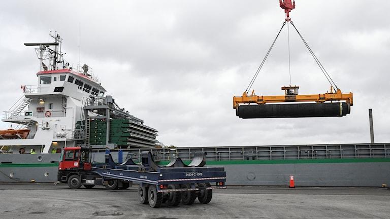 A crane lifting a pipe onto a nearby cargo ship.