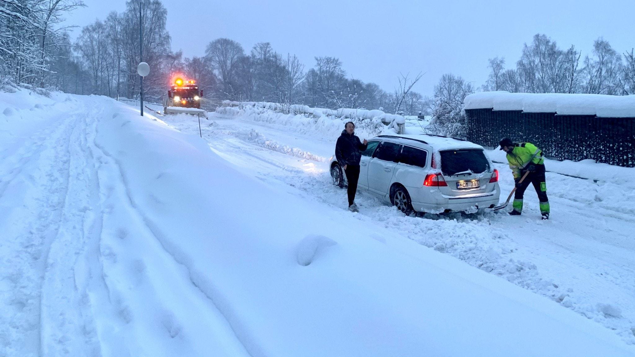 En man i varselkläder skottar loss en vit bil i en backe. En man i mörka kläder står bredvid bilen och tittar på. Foto: Karin Lönnå/Sveriges Radio