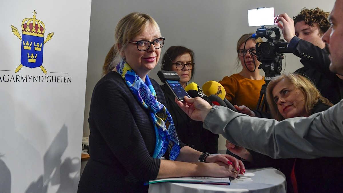 A woman in glasses speaking to a gaggle of reporters.