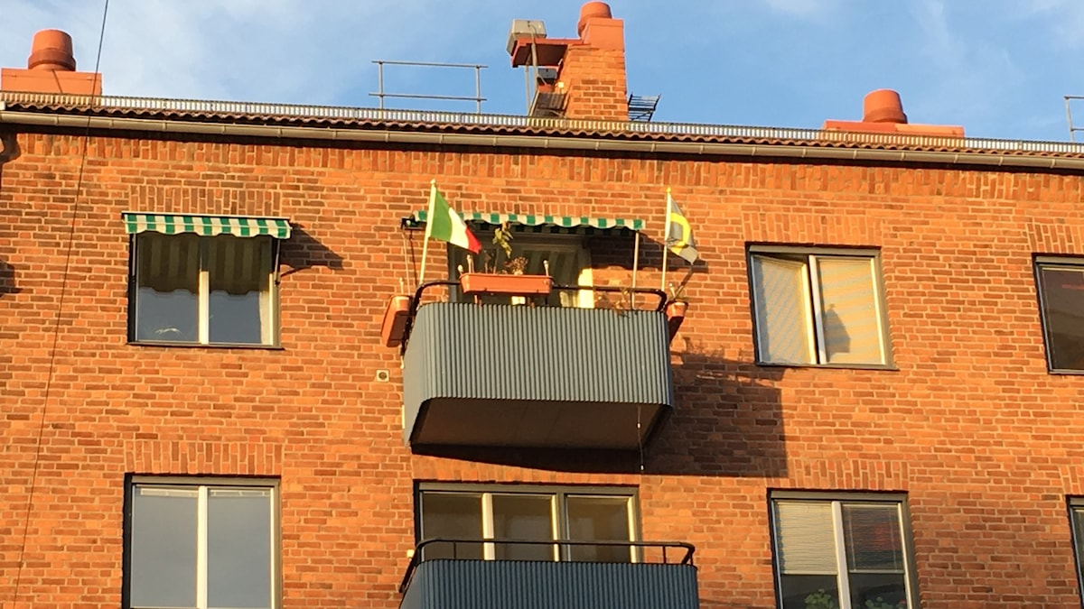 An Italian and a Swedish flag wave on a balcony in Västerås, where one of the first waves of immigrant labor came from Italy after World War II.
