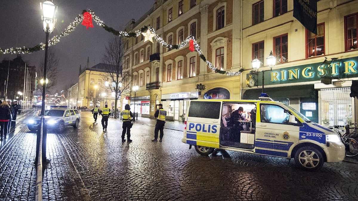 Police have cordoned off a street that has Christmas lighting across it.