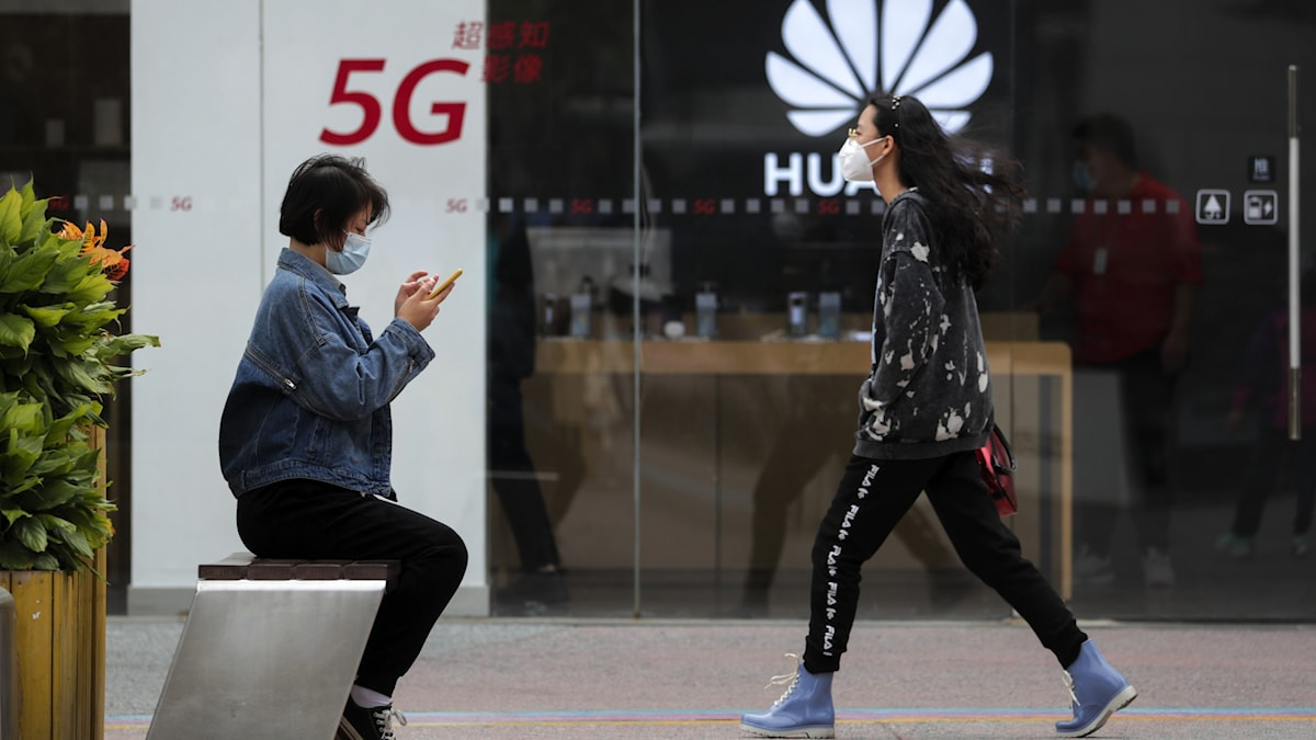 People walk past a building with the sigh 5G Hauwei showing