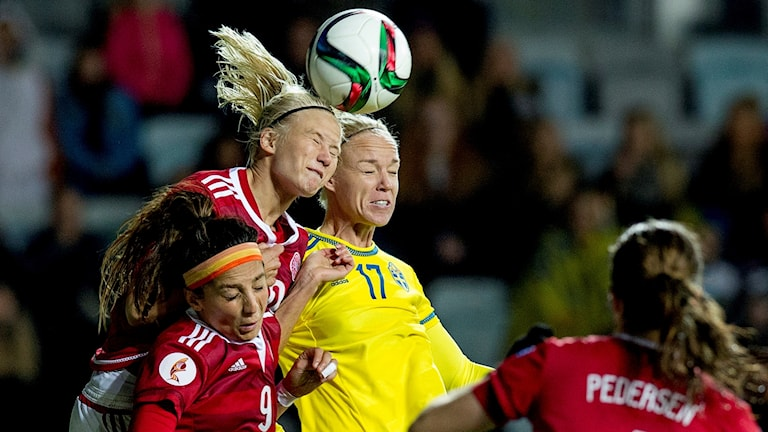 Women playing football, struggling for the ball.