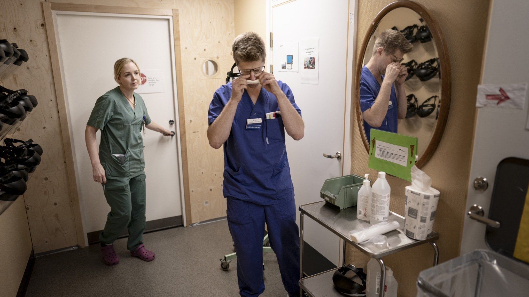 A person wearing green scrubs has her hand on a doorknob, while a person wearing blue scrubs is reflected in a mirror.