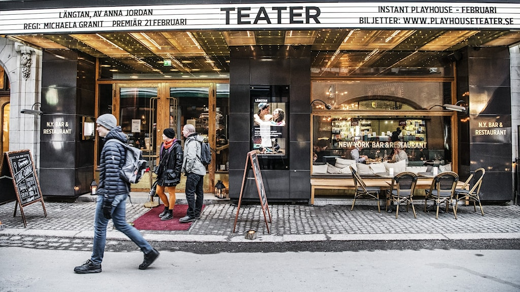 A pedestrian on a city street passes a theater marquee.