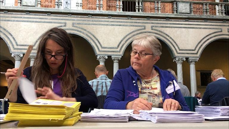 two women sort through stacks of envelopes