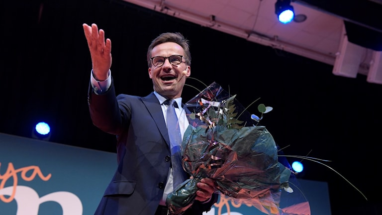 Man with glasses and a bunch of flowers on a stage.