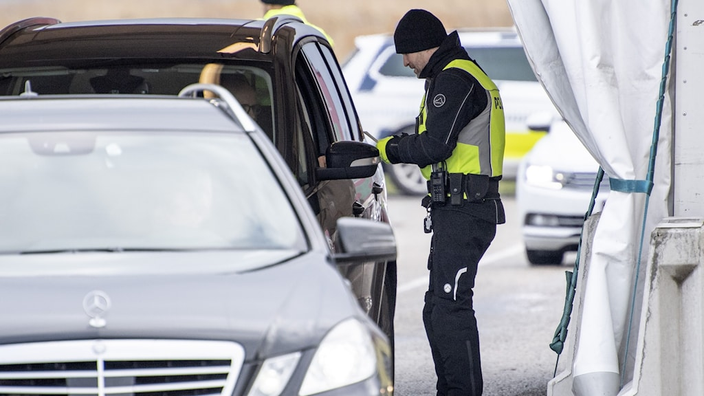 A guard checking someone's ID crossing into Denmark