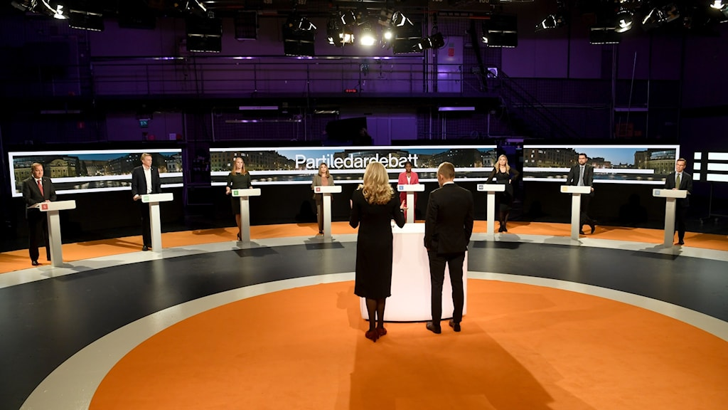 An image of people standing at lectern on a TV studio sound stage.