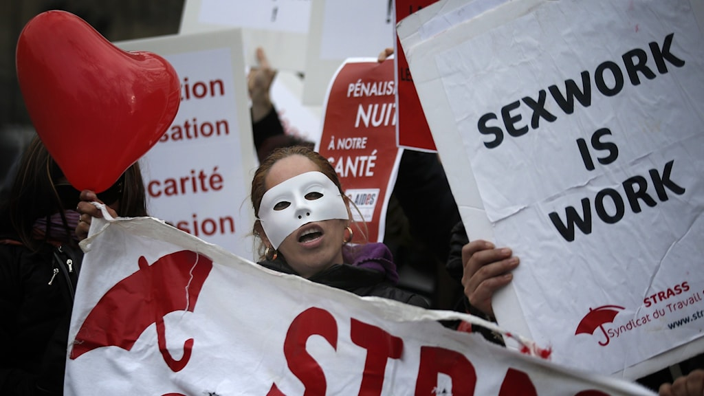 A woman wearing a mask and holding signs outside.