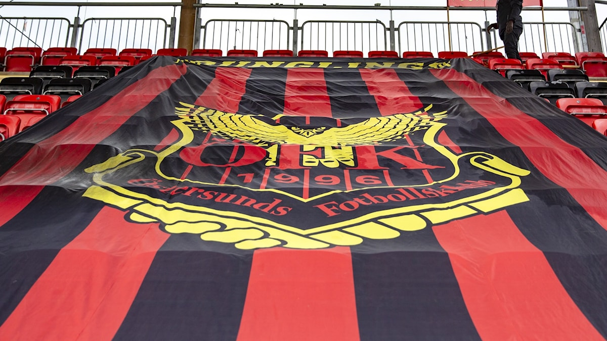 Huge red-and-back football banner over seats at a stadion.