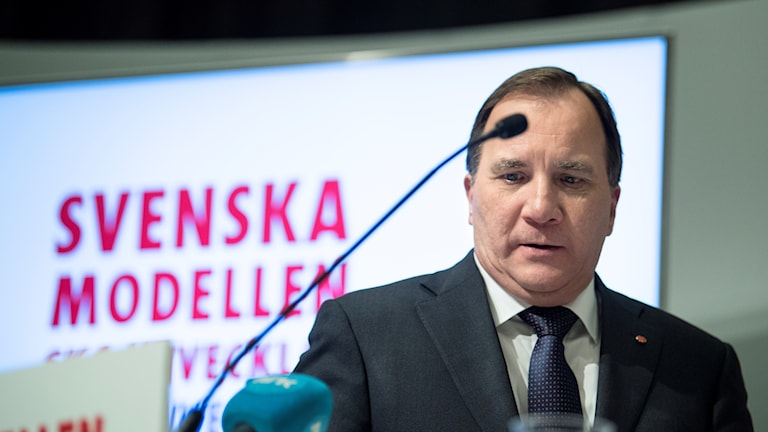 Prime Minister Stefan Löfven stands in front of a microphone.