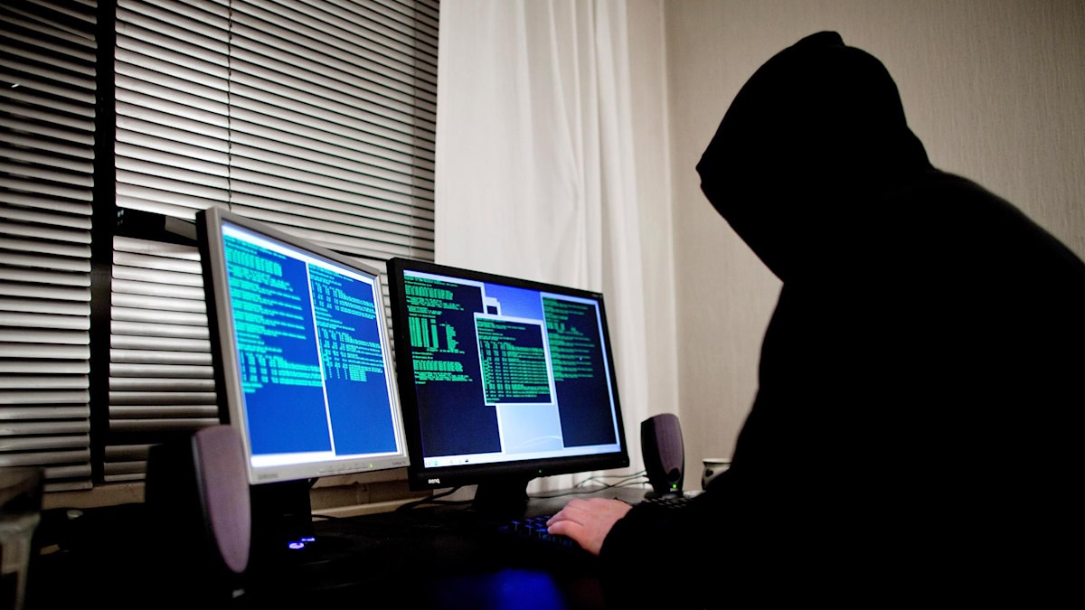 Anonymous man dressed in black using a computer