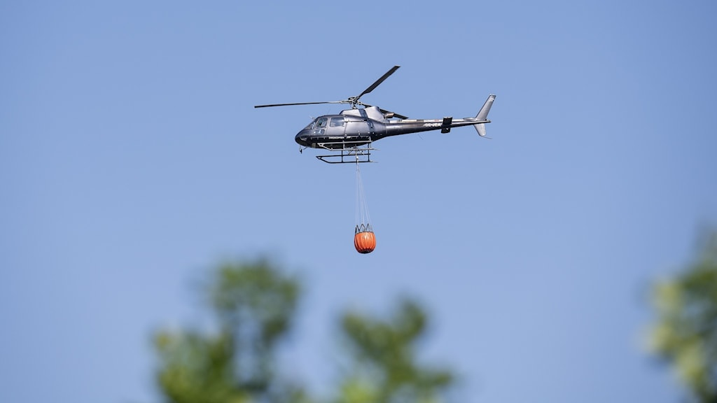 Helicopter flying with waterbombs above wildfires