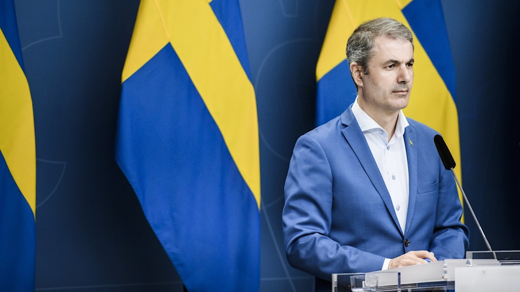 A man standing in front of Swedish flags.