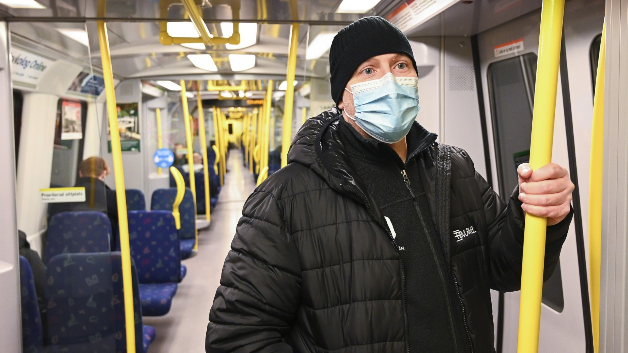 A person standing in an underground train, wearing a medical mask