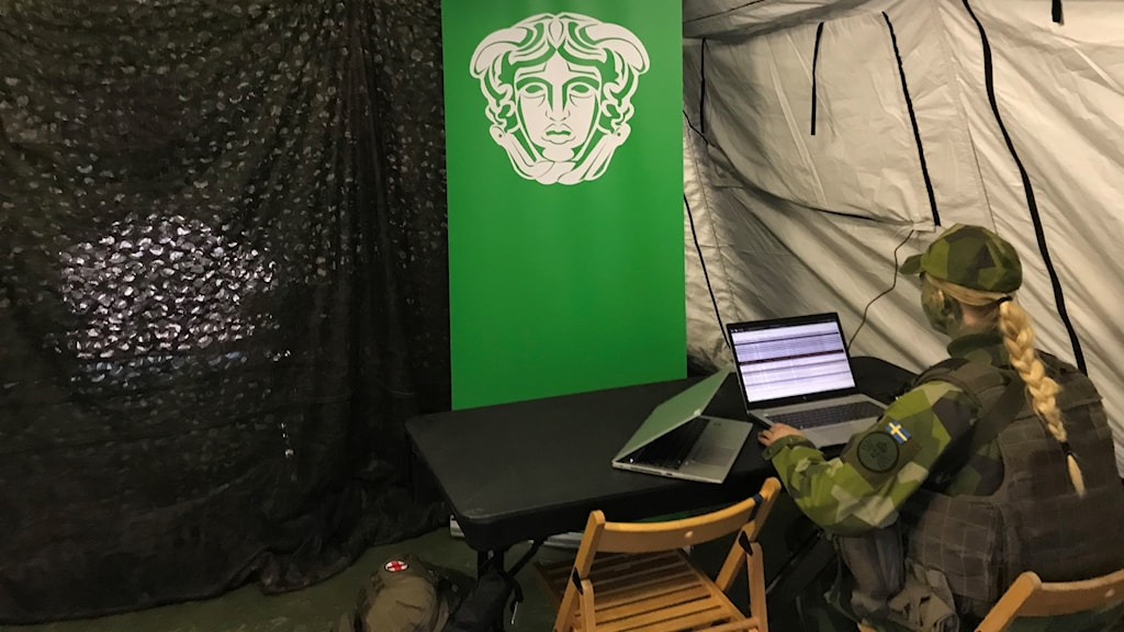 A soldier sitting in a tent looking at a laptop
