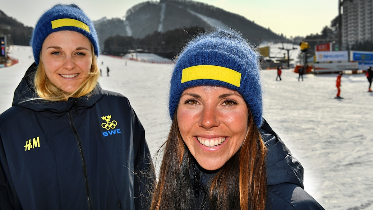 two women pictured on the snow, wearing swedish Olympics uniforms