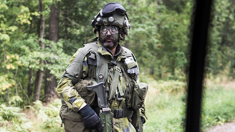 Soldier in full gear and a face mask.