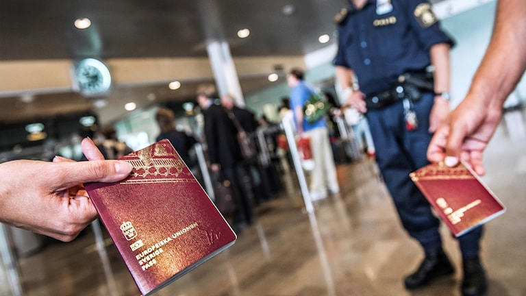 passports shown to camera, border police in background.