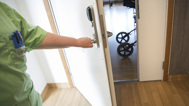 A person wearing medical clothes opening a door to show a rullator.
