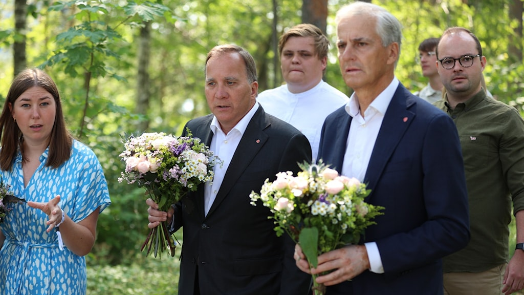 Three people holding flowers to place at a memorial.