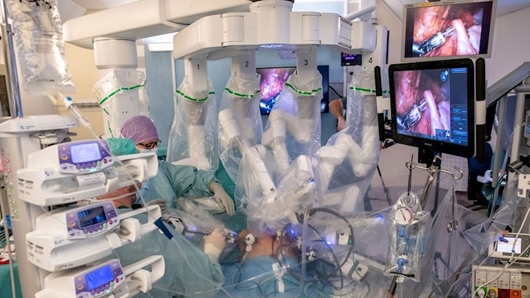 Ongoing surgery with surgeon to the left, who is controlling part of the robot, and donor patient to the right.