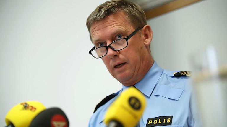 Man in police uniform in front of cameras