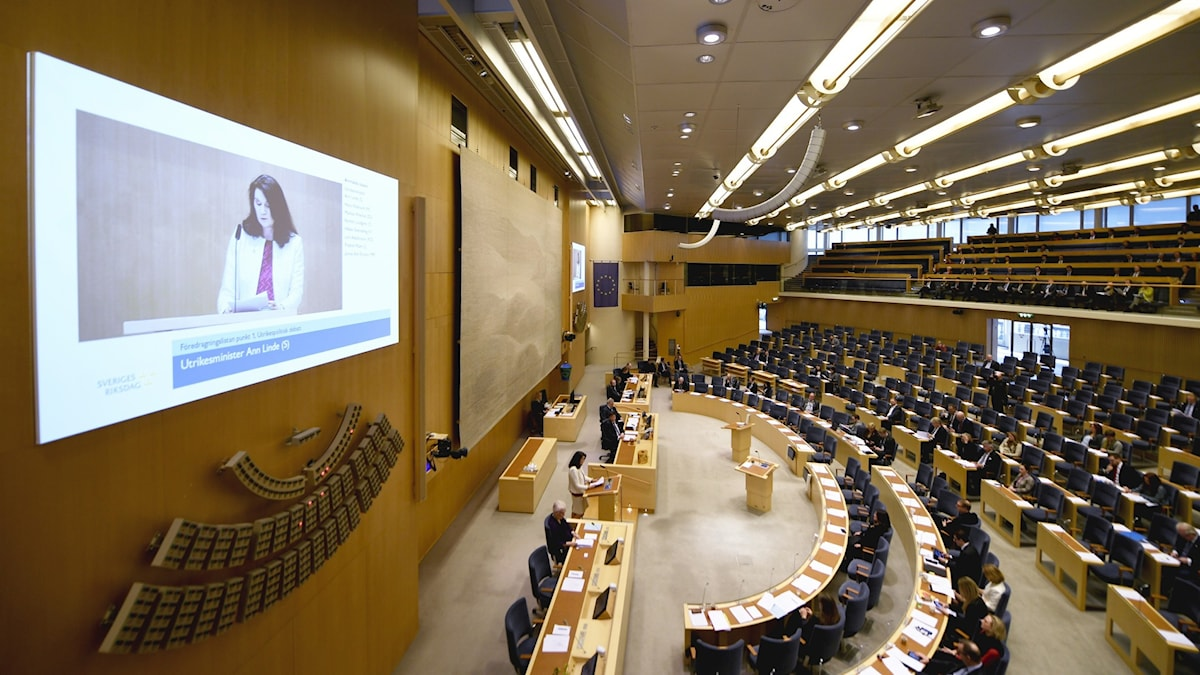 A bird's eye view of the Swedish parliament, with a screen showing Ann Linde reading out the foreign policy declaration.